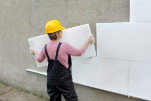 Укладка листов пенопласта на поверхность обрабатываемых стен