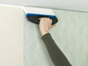 Для разглаживания полотна лучше использовать резиновый валик или широкую щетку с жесткой щетиной, которая качественно удаляет из-под обоев пузырьки воздуха.