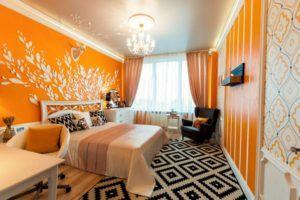 Изящная роспись белого цвета на оранжевой стене спальни