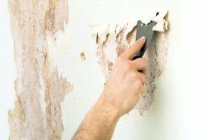 Процесс очистки стен при помощи шпателя.