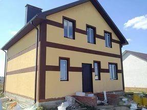 Дом, отделанный панелями, изготовленными из древесного или бумажного волокна, выглядит весьма привлекательно.