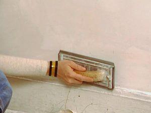 Перед окрашиванием стены шкурят мелкой наждачной бумагой или сеткой, закрепленной на специальной форме (терке).